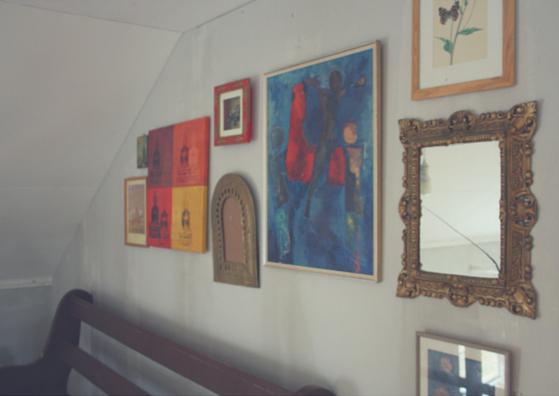 tavelvägg med speglar och tavlor