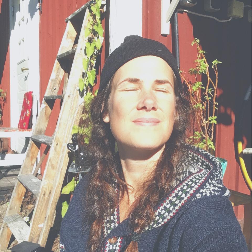 njuter i solen på altan till huset